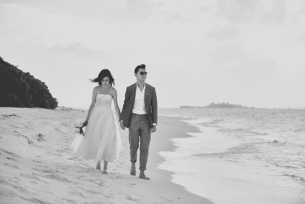 Couple walking on the beach in black and white