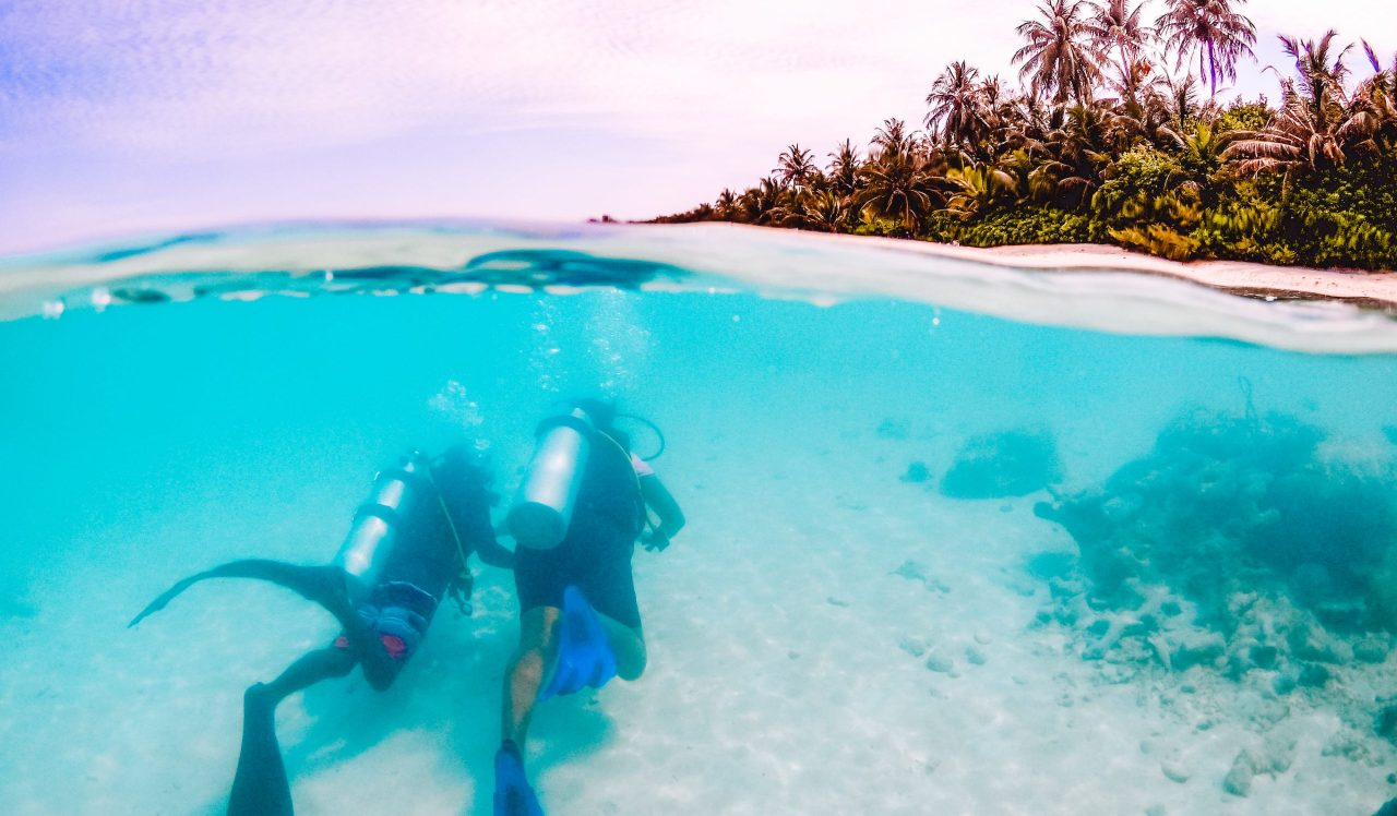 Scuba divers during a PADI Open Water course with Dhigurah in the background. Excursions in the Maldives - Diving with whale sharks