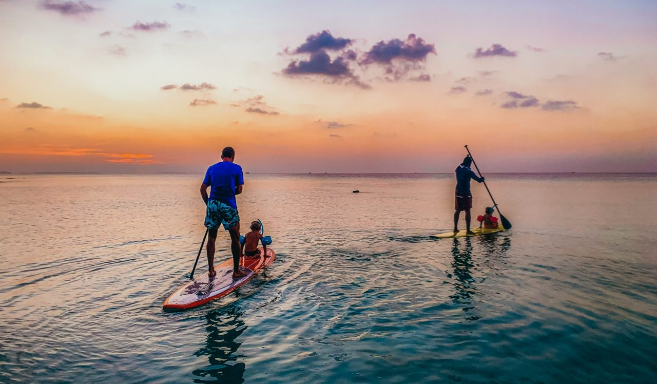 Family on two Stand Up Paddle boards during sunset